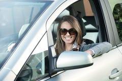 有太阳镜的可爱的妇女在她的汽车 免版税库存照片