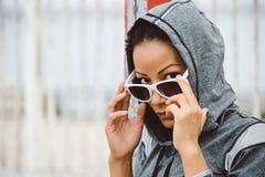 有太阳镜的坚韧看起来的都市健身妇女 免版税图库摄影
