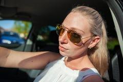 有太阳镜的妇女在汽车 免版税库存照片