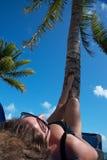 有太阳镜的妇女晒日光浴在棕榈树下的 免版税图库摄影