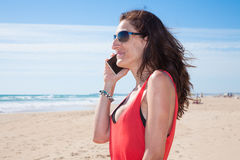 有太阳镜的妇女谈话在电话在海滩 免版税库存照片