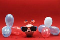 有太阳镜的存钱罐有美国旗子的和蓝色,红色和白色党气球和两面小美国旗子在红色背景 免版税图库摄影