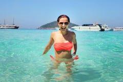 有太阳镜的少妇在与smil的透明的海水 库存图片