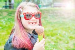 有太阳镜的微笑的女孩吃冰淇淋的在公园 免版税库存图片