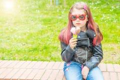 有太阳镜的微笑的女孩吃冰淇淋的在公园 免版税图库摄影