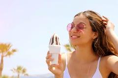 有太阳镜的微笑的美女在海滩吃与棕榈树的冰淇淋在backgroud o 免版税库存照片