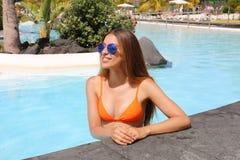 有太阳镜的性感的比基尼泳装女孩在热带游泳场里面 免版税图库摄影