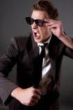 有太阳镜的恼怒的商人 免版税图库摄影