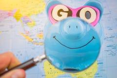 有太阳镜的愉快的存钱罐在与准备好magnifyed明亮的微笑的世界地图上去花下次旅行的储款 图库摄影
