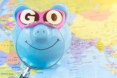 有太阳镜的愉快的存钱罐在与准备好magnifyed明亮的微笑的世界地图上去花下次旅行的储款 免版税图库摄影