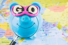 有太阳镜的愉快的存钱罐在与准备好magnifyed明亮的微笑的世界地图上去花下次旅行的储款 库存图片