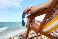 有太阳镜的手在海滩 库存图片
