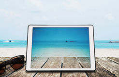 有太阳镜的数字式片剂在热带海滩的木书桌上 免版税库存图片