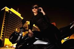 有太阳镜的美丽的少妇谈话在电话和倾斜在她的摩托车的在晚上 库存图片
