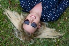 有太阳镜的美丽的白肤金发的妇女 免版税库存照片
