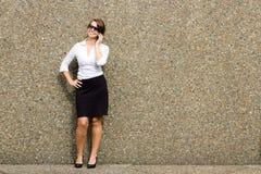 有太阳镜的老练妇女使用流动巧妙的电话 免版税库存照片