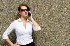 有太阳镜的老练妇女使用流动巧妙的电话 库存照片