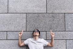 有太阳镜的英俊的年轻人指向,查寻和微笑,站立对灰色墙壁 免版税图库摄影