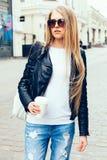 有太阳镜的走在欧洲街道上的一个年轻美丽的白肤金发的女孩的画象用咖啡 室外 温暖的颜色 库存照片
