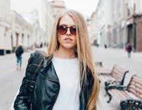 有太阳镜的走在欧洲街道上的一个年轻美丽的白肤金发的女孩的画象  室外 温暖的颜色 库存图片