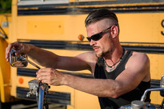 有太阳镜的顽固的家伙懒洋洋地倚靠在他的砍刀摩托车的 库存图片