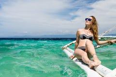 有太阳镜的年轻欧洲妇女坐小船在热带绿松石海并且得到棕褐色晴天 免版税库存照片