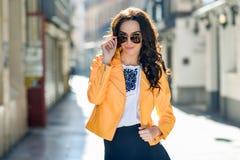 有太阳镜的年轻深色的妇女在都市背景中 免版税库存照片