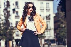 有太阳镜的年轻深色的妇女在都市背景中 库存照片