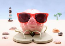 有太阳镜的滑稽的存钱罐,假日背景 免版税库存图片