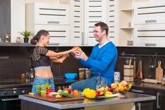 有夫妇的乐趣厨房年轻人 免版税图库摄影