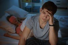有失眠的年轻人坐床 图库摄影