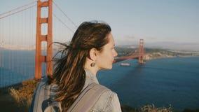 有头发的平安的年轻旅游妇女吹在强风享受史诗日落全景的在偶象金门大桥 影视素材