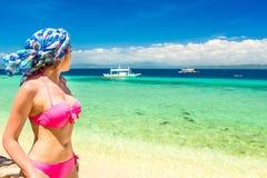 有头巾的妇女观看从一个白色海滩的惊人的热带海视图 免版税库存照片