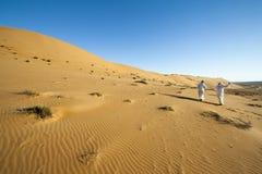 有头巾的阿拉伯人,沙漠走在沙漠的导游 免版税库存照片