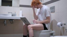有头疼的人使用膝上型计算机在卫生间,洗脸台里 库存图片