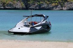 有奇怪地形状的高速游览小船在海滩附近 库存照片