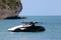 有奇怪地形状的高速游览小船在海滩附近 免版税库存照片