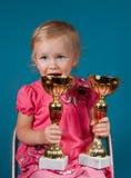 有奖杯的愉快的小女孩 库存照片