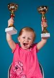 有奖杯的愉快的小女孩 库存图片