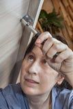 有套筒扳手的妇女手拉紧坚果,特写镜头 免版税库存照片