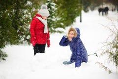 有女儿修造的母亲一个雪人在公园 库存照片