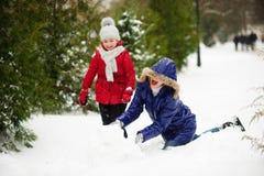 有女儿修造的母亲一个雪人在公园 免版税库存图片