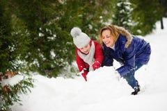 有女儿修造的母亲一个雪人在公园 免版税库存照片