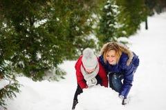 有女儿修造的母亲一个雪人在公园 库存图片