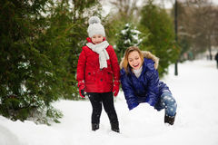 有女儿修造的母亲一个雪人在公园 免版税图库摄影
