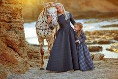 有女儿和呈杂色的马的妇女 免版税库存照片