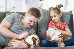 有女儿和小狗英国牛头犬的有同情心的爸爸 图库摄影