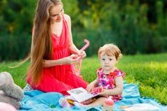 有女儿和玩具的妈咪在野餐在公园 免版税图库摄影