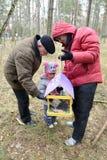 有女儿和祖父的年轻人投入了五谷我 库存图片