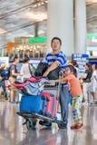 有女儿和被包装的台车的人在北京首都国际机场 免版税库存图片